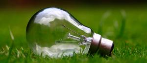 Save electricity, Blog on Saving electricity bills - Bulb on grass
